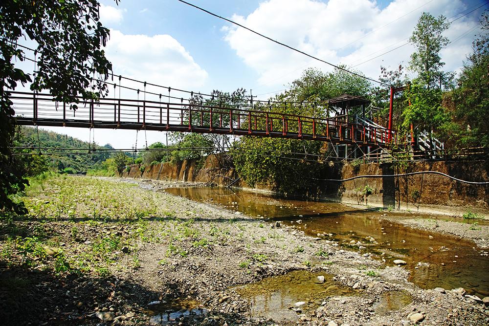 金興吊橋的紅色橋身,高吊在綠意山巒環繞之間,格外醒目。(攝影/曾信耀)