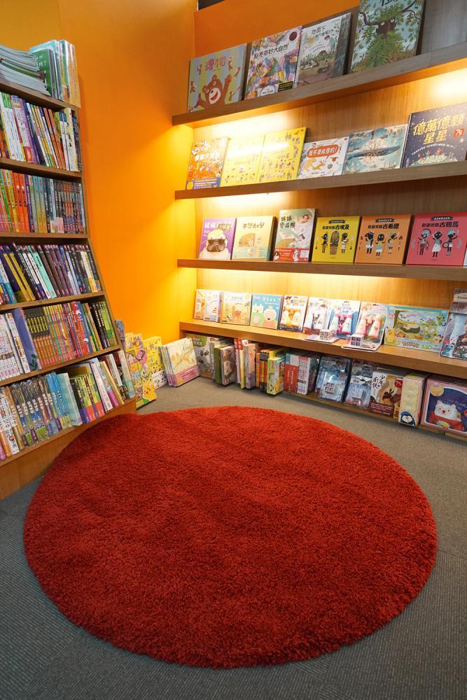 兒童閱讀區鋪上紅色長毛地毯,讓親子享受放鬆親暱的共讀時光。(攝影/李曉萍)