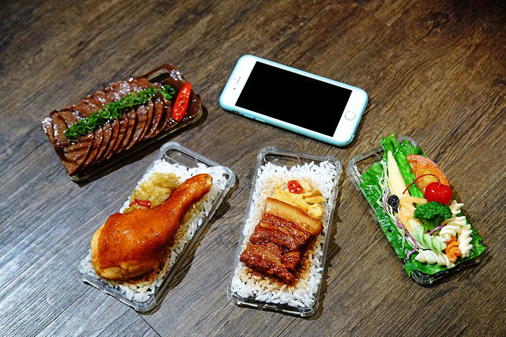 利用食物模型開發各式文創商品,吃貨必備滷肉飯、雞腿飯手機殼。(攝影/曾信耀)