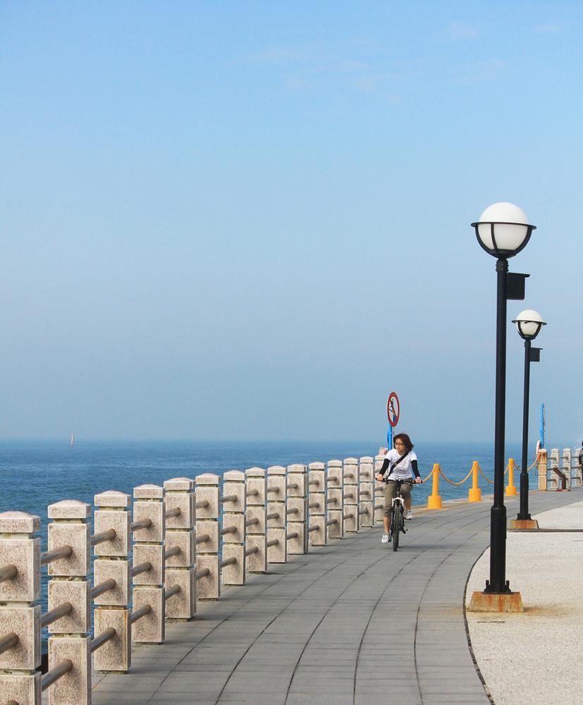 遊客在海岸公園吹海風享受悠閒步調。