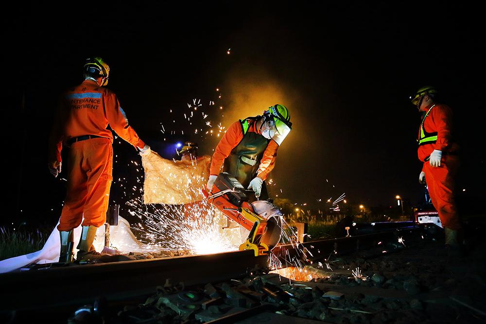 鋸軌現場火花四射,顧及周邊野草眾多,上工前需要先舖上防火布並備有水源及滅火設備,避免危險。(攝影/Carter)