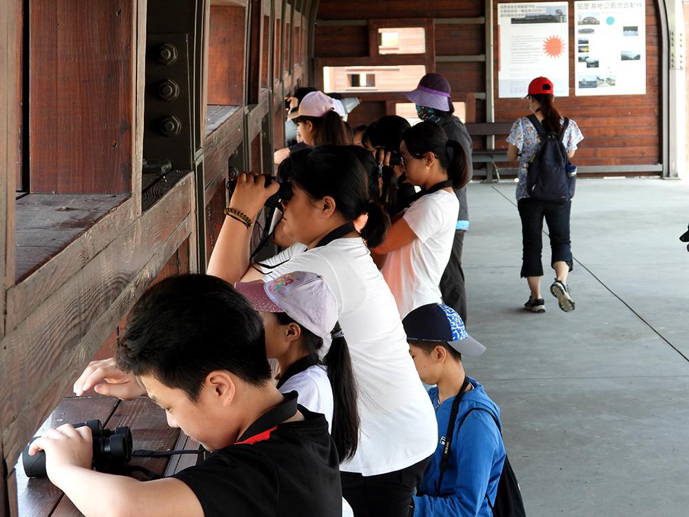 孩子們拿著望遠鏡,在賞鳥亭裡觀水鳥、聽解說。(圖片提供/高雄市茄萣區觀光發展協會)