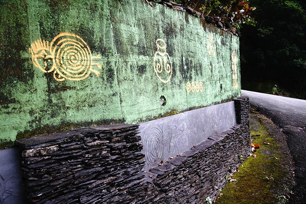 進入萬山部落,由馬樂創作的萬山岩雕引道連綿數百公尺。(攝影/曾信耀)