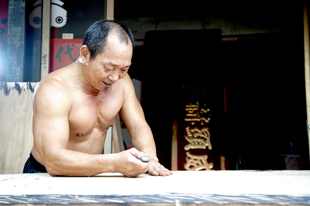 打赤膊製作匾額的吳崑章,是鳳山佛具街「三民路」生活裡的一道日常風景。(攝影/曾信耀)