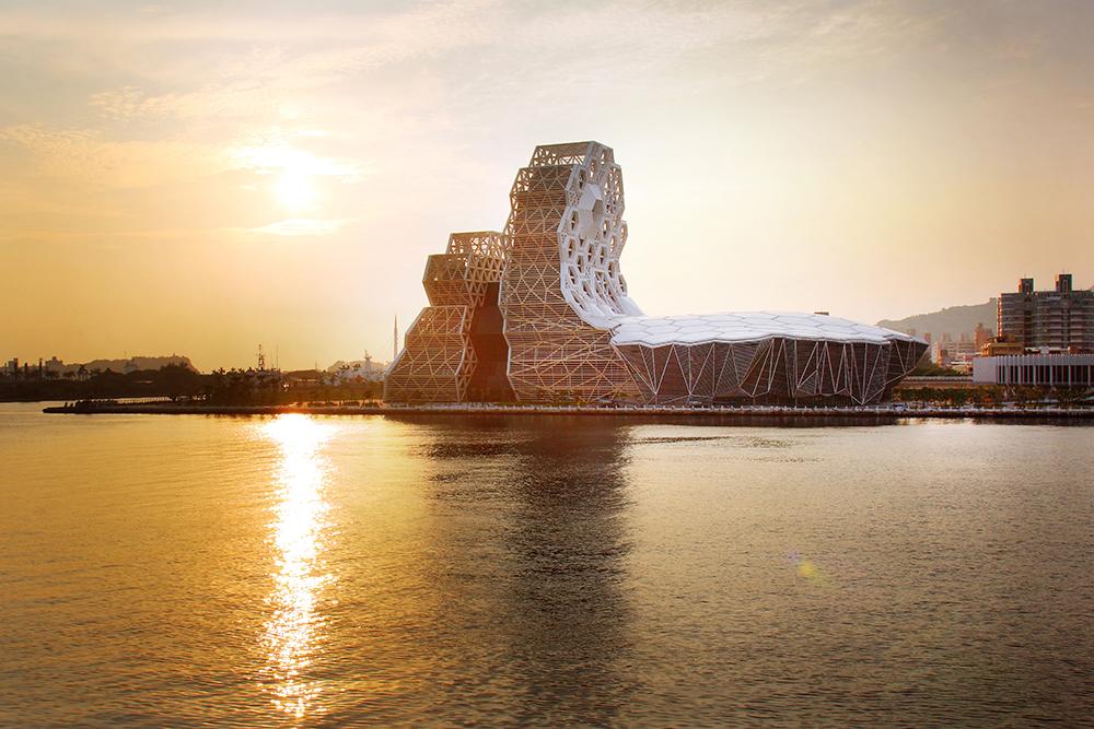 落日餘暉,橙色光芒隱在高雄流行音樂中心,與水波相映,煞是美麗。(攝影/Carter)