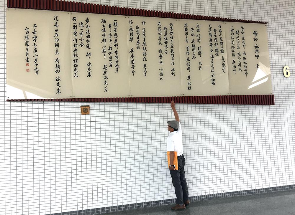 位於禮堂外牆巨幅的詩壁,呈現由名書法家薛平南書寫余光中的詩-等你 在雨中。