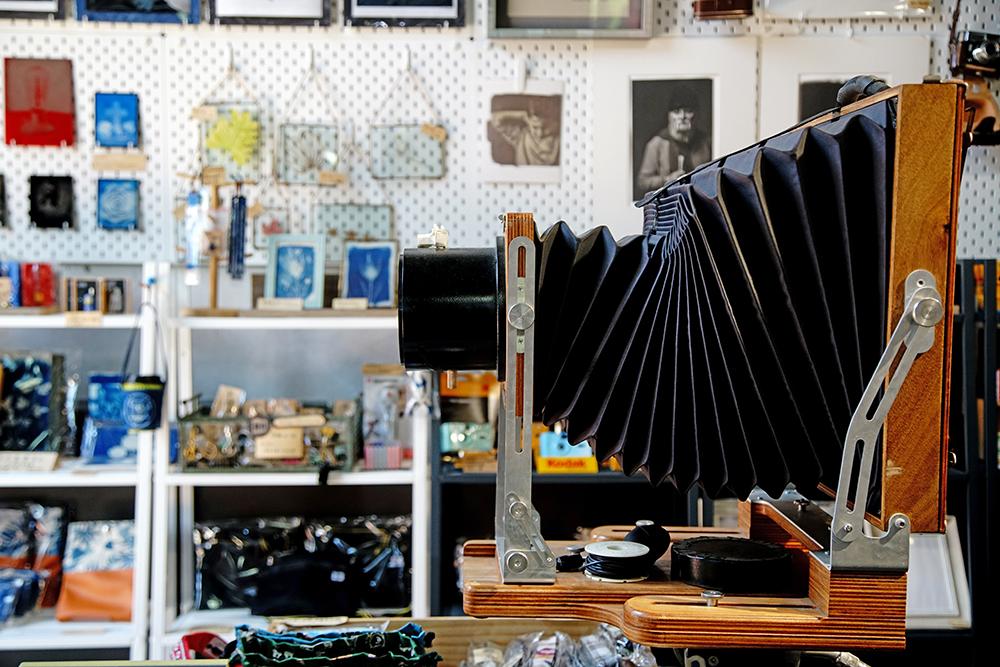 工作室內展示大型蛇腹相機,可看到店外的景象,了解針孔成相的攝影原理。(攝影/曾信耀)