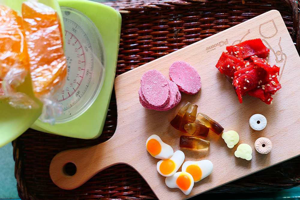 蜜地瓜、鐵板燒小捲,還有整包購買較為昂貴的軟糖,都是人氣商品。(攝影/李瑰嫻)