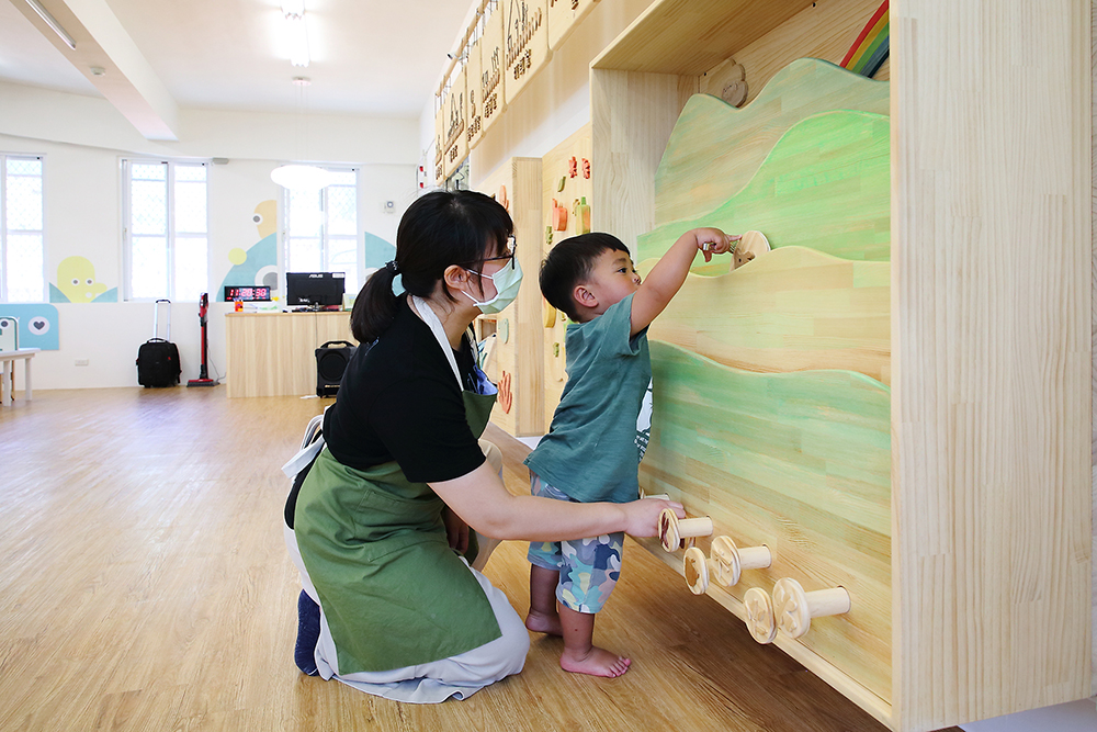 孩子在家長與社工引導下探索環境,透過遊戲打開視覺、觸覺等知覺潛能。(攝影/Carter)