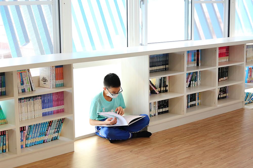 孩子們很喜歡在木板平台上看書,一個人窩在城垛書櫃的秘密基地,安靜地閱讀。(攝影/Carter)